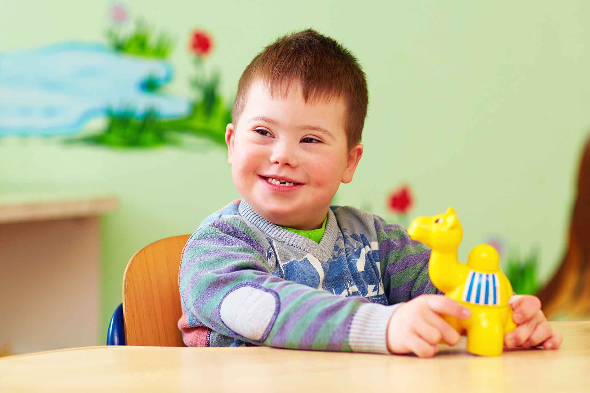 a Child with Down Syndrome plays with a toy